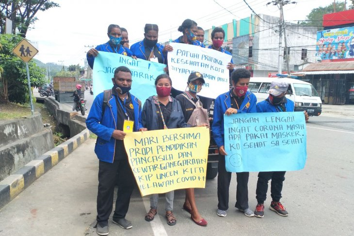 Uncen students distribute masks